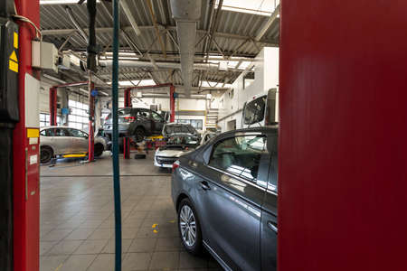 Luxury cars being repaired in a modern garage. View through red door