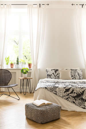 A bed with leaf decor linen, a rattan and metal chair and a pouf in a white wall bedroom interior. Real photo.