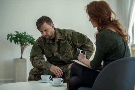 Sad soldier in uniform during meeting with psychotherapist in the office