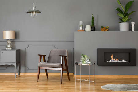 Grey armchair next to silver table in elegant living room interior with fireplace and lamp. Real photo