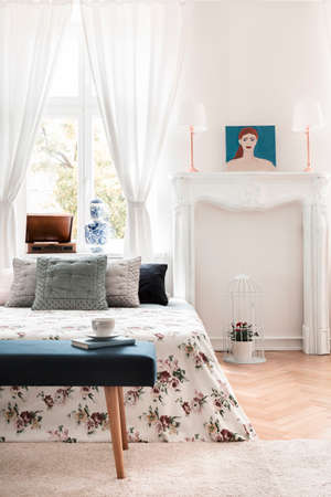 Blue bench in front of patterned bed with pillows in white bedroom interior with poster. Real photo