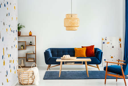 Lamp above wooden table in colorful living room interior with armchair and blue sofa. Real photo