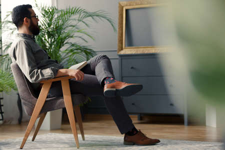 Low angle of hipster sitting on wooden armchair in grey vintage interior with plant Stock Photo
