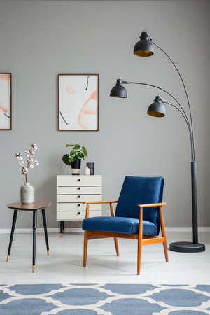 Flowers on wooden table next to blue armchair and lamp in grey living room interior. Real photo Stok Fotoğraf - 107108365