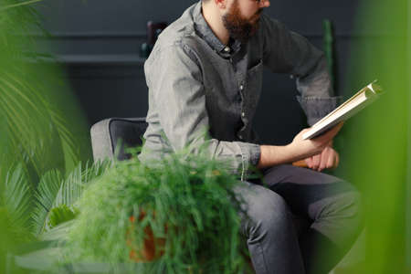Man in grey shirt reading a book while relaxing at home with plants