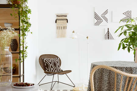 Patterned cushion on chair and plant on table in white boho living room interior with posters. Real photo Stock Photo - 107108478