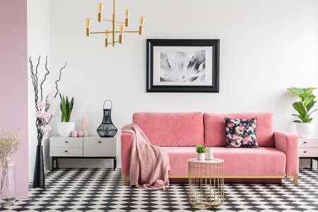 Roze deken op bank in wit woonkamer interieur met planten en geruite vloer. Echte foto