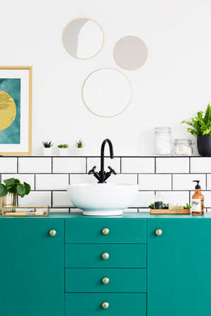 Turquoise cupboard, sink, black faucet and round mirror in a modern bathroom interior. Real photo