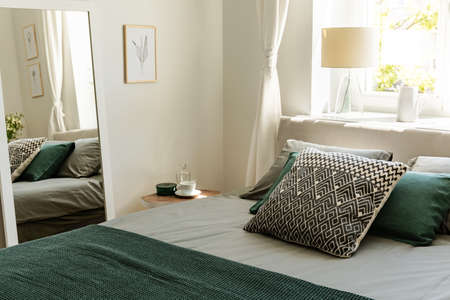 Patterned and green pillows on bed in simple bedroom interior with poster and mirror. Real photo