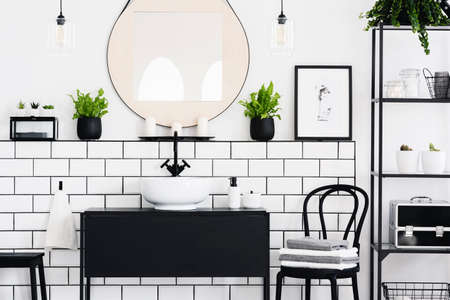 Real photo of black and white bathroom interior with a mirror, cupboard, chair and plants