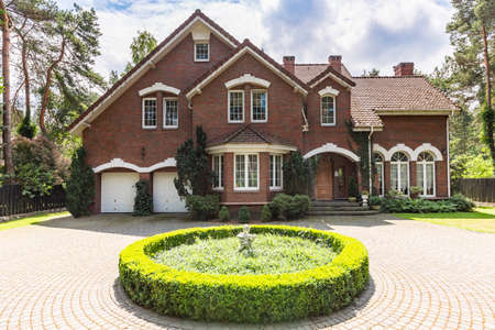 Front view of a red brick English style classic house with a steep roof, large windows and a circular driveway with a flowerbed decoration in the front. Stockfoto