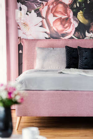 Black and grey pillows on pink bed in feminine bedroom interior with flowers on the wall. Real photo