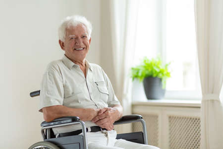 Smiling disabled senior man in a wheelchair alone at home
