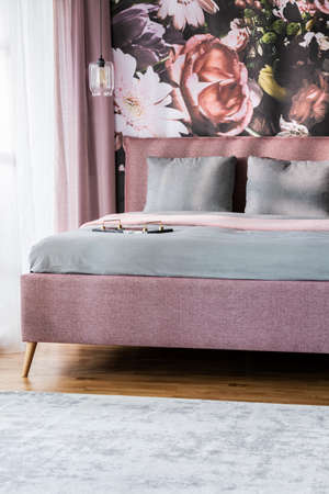 Grey sheets on pink bed in hotel bedroom interior with flower print on the wall. Real photo Stock fotó