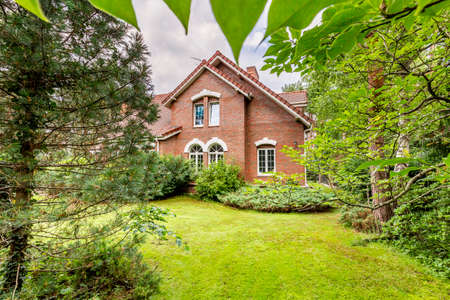 Backyard with green grass, trees and evergreens of a traditional English design country house in red brick