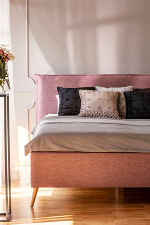 Pillows on bed in grey and pink bedroom interior with flowers and wall with molding. Real photo