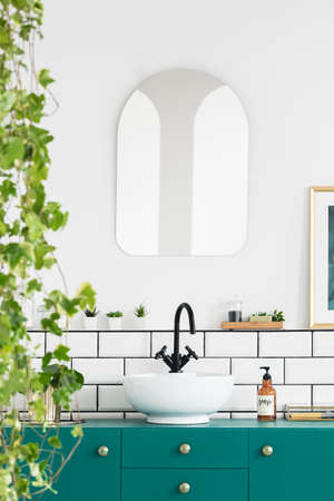 Close-up of leaves with a mirror, wash basin, black faucet and turquoise cupboard in a bathroom interior. Real photo