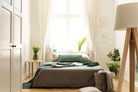 Lamp and white door in bright bedroom interior with plants and window above bed. Real photo