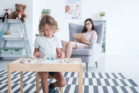 Boy sitting at the table and playing with building blocks while his counselor is taking notes Stock Photo