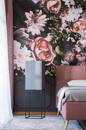 Flowers wallpaper in dark bedroom interior with black table next to pink and grey bed. Real photo Stock fotó
