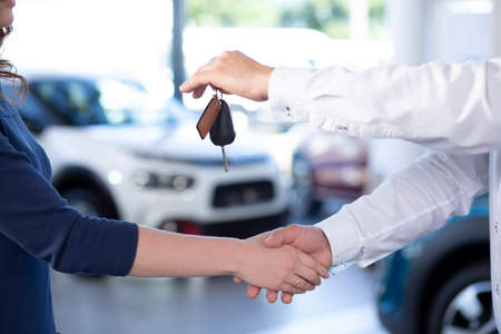 Close-up of car dealer shaking buyers hand and giving keys after transaction