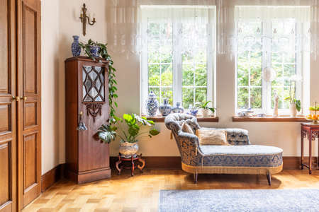A luxurious living room interior with a couch and a wooden cabinet standing on a parquet against two large windows. Real photo. Stock Photo - 107212660