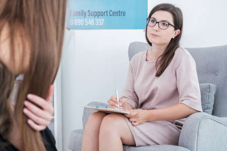 Therapist holding a pen and papers, and talking to her patient with long hair