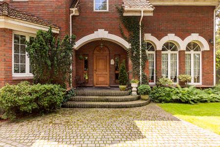 Camino empedrado y escalones que conducen a una elegante entrada con puertas de madera ornamentadas y ventanas laterales en una mansión de ladrillo rojo de estilo inglés.