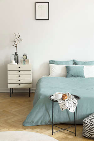 Real photo of a womans bedroom interior with white walls, parquet floor, pale sage green bedding and drawer cabinet. Stockfoto