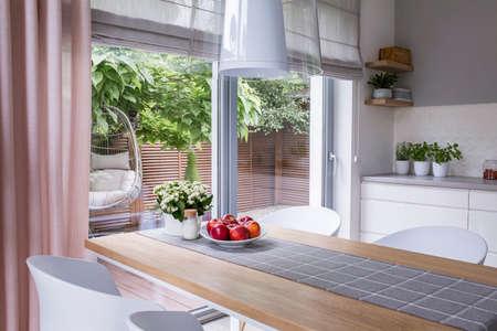 Echtes Foto eines modernen Esszimmerinnenraums mit Tisch, Apfelteller und Blick auf eine Terrasse mit Schaukel Standard-Bild