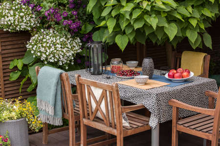 Garden table full of fruit, wooden chairs on a terrace surrounded by plants and flowers Reklamní fotografie - 107535254