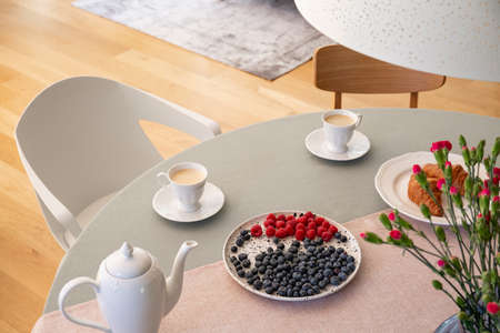 Real photo with high angle of dining table with fresh flowers, jug, coffee cups and plate with fruits