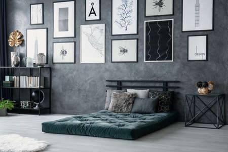 Table next to green mattress with cushions in grey bedroom interior with posters. Real photo