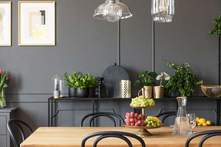 Lamps above wooden table and black chairs in grey dining room interior with poster. Real photo