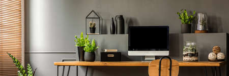 Fresh green plants, decoration and empty monitor screen placed on a wooden desk standing next to the window with blinds in grey living room interior