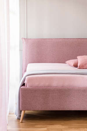 Lavender purple blanket on a pink bed with upholstered headboard in a beige bedroom interior with natural light Stock Photo