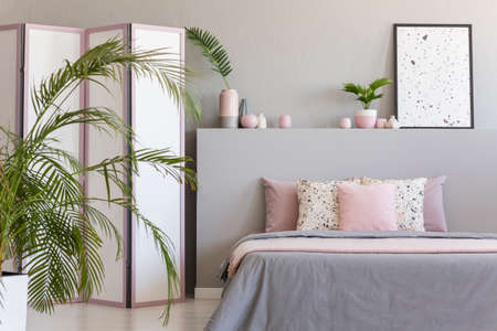 Pink pillows on grey bed in pastel bedroom interior with palm and poster on bedhead. Real photo