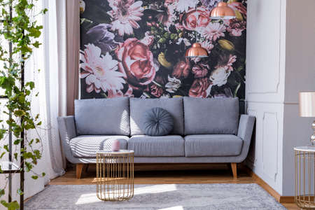 Sunlit, gray sofa by a floral print wall in the nook of a feminine living room interior with golden accessories Foto de archivo - 107535332