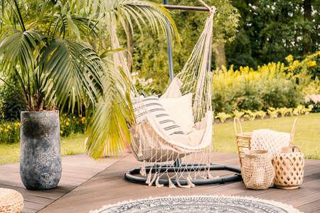 Verano en el verde jardín con una hamaca y una palmera en una terraza. Foto de archivo