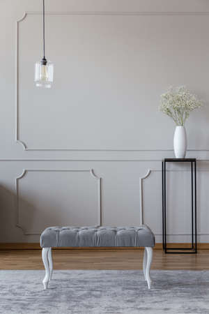 Elegant upholstered bench on a gray rug and flowers on a black table standing in a beige living room interior with molding
