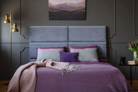 Close-up of stylish, luxurious hotel room interior with pink blanket on ultra violet bed standing against dark wall with molding. Real photo
