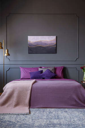 Elegant hotel room interior real photo with painting on the wall and a big bed in the center