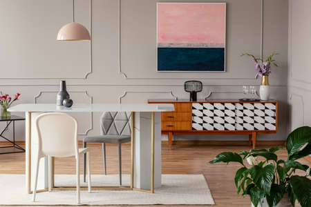 White chair and marble table under pink lamp in eclectic living room interior with painting above cabinet. Real photo Banque d'images