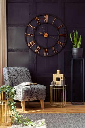 Grande orologio sul muro nero, poltrona, tavolo e pianta in un soggiorno interno. Foto reale