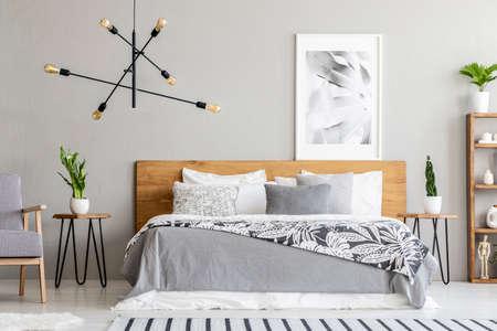 Manta estampada en cama de madera y sillón en el interior del dormitorio gris con cartel y plantas. Foto real