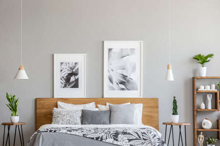 Posters above wooden bed between tables with plants in grey bedroom interior with lamps. Real photo Archivio Fotografico - 107307796