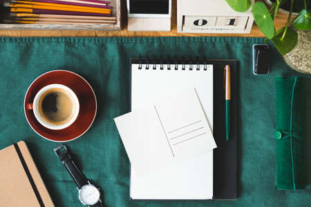 Top view of a coffee, notepad, postcard and watch on the green cloth Stock Photo