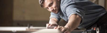 Panorama des professionellen Tischlers mit Werkzeuggürtel während der Tischlerarbeiten Standard-Bild