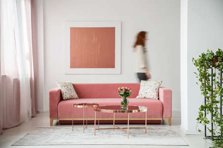Blurred person against the wall with painting in white flat interior with plant and millenial pink couch. Real photo 스톡 콘텐츠
