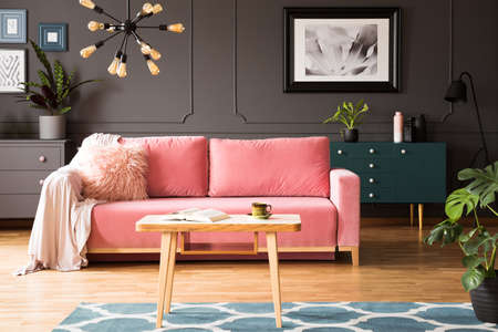 Poster on grey wall in living room interior with pink couch and wooden table on carpet. Real photo